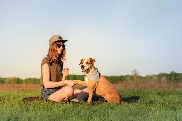 Vrouwelijke hondeigenaar en opgeleide staffordshire terriër die poot geeft bij gazon