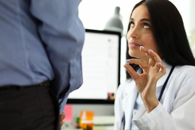 Vrouwelijke huisarts in ziekenhuis kantoor aanbieden aan kleine blauwe pil man
