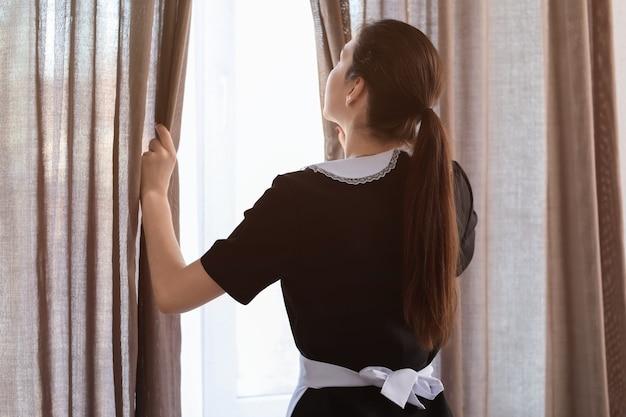 Vrouwelijke huishoudster gordijnen openen op raam in kamer