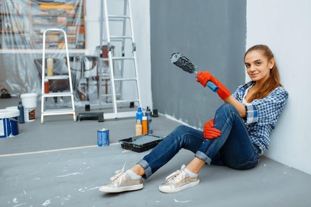 Vrouwelijke huisschilder met verfroller zittend op de vloer na het werk. huisreparatie, gelukkige vrouw die flatrenovatie doet