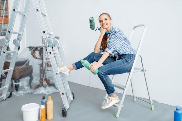 Vrouwelijke huisschilder met verfroller zittend op een ladder. huisreparatie, gelukkige vrouw die appartementsrenovatie doet