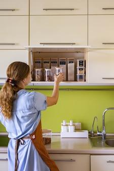 Vrouwelijke huisvrouw die glazen potten vol gezonde voeding noten granen granen op kastplank plaatst