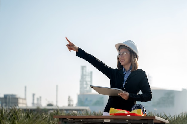 Vrouwelijke industrieel ingenieur in een bouwvakker die aan olieraffinaderij en elektriciteitscentraleplaats, industrie, ingenieur en veiligheidsconcept werkt.