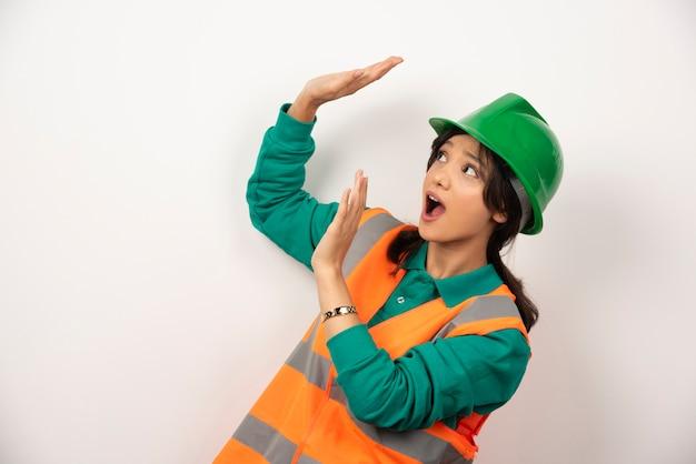 Vrouwelijke industrieel ingenieur in uniform met helm op witte achtergrond.