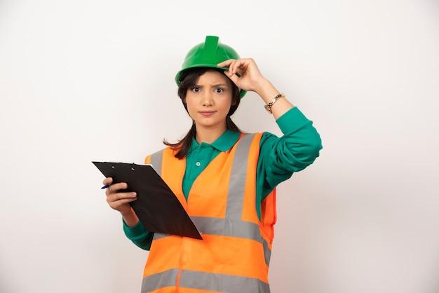 Vrouwelijke industrieel ingenieur in uniform met klembord op witte achtergrond.