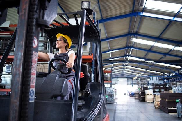 Vrouwelijke industriële chauffeur heftruck machine in het magazijn van de fabriek