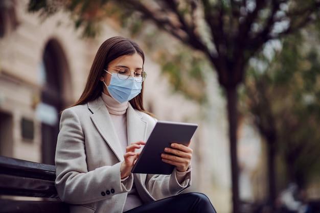 Vrouwelijke influencer met gezichtsmasker zit buiten op de bank en gebruikt tablet om te kijken wat er op sociale media gebeurt