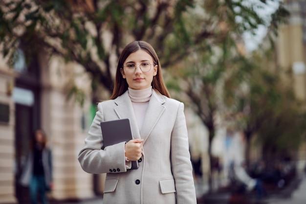 Vrouwelijke influencer permanent op straat en tablet in handen te houden. millennials en hun sociale leven.