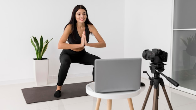 Vrouwelijke influencer thuis vloggen tijdens het sporten