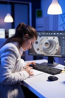 Vrouwelijke ingenieur-architect die in een modern cad-programma werkt aan een bureau in een start-up kantoor