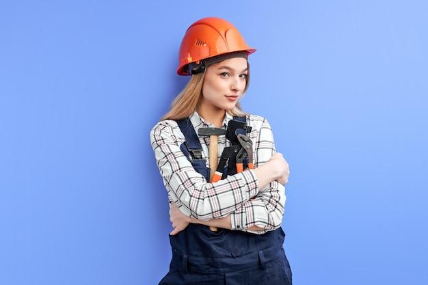 Vrouwelijke ingenieur constructor tools voor huishouden in handen houden en camera kijken