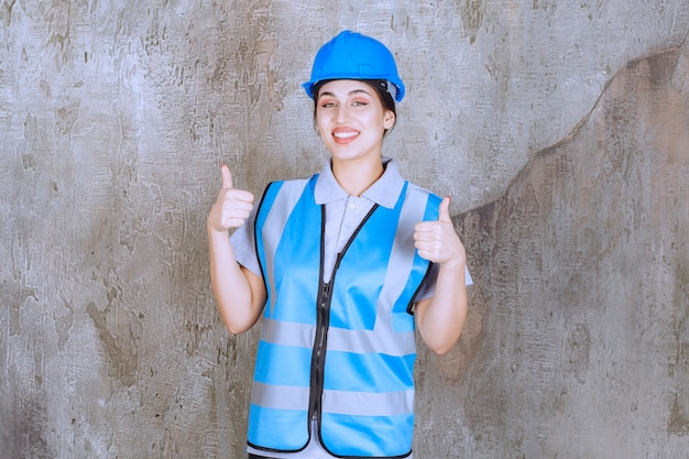 Vrouwelijke ingenieur die blauwe helm en uitrusting draagt en positief handteken toont.