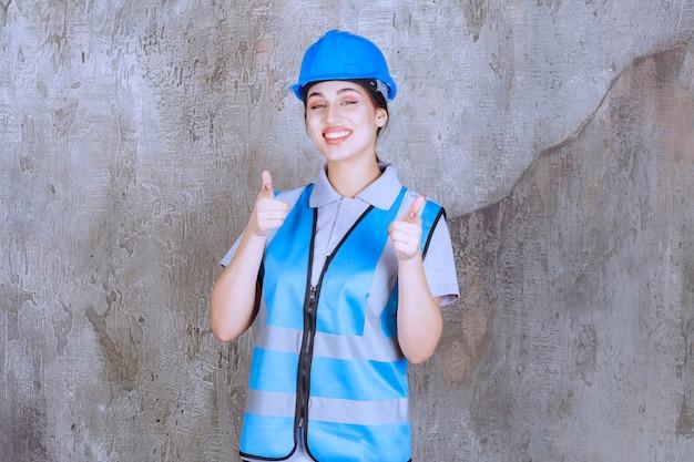 Vrouwelijke ingenieur die een blauwe helm en uitrusting draagt en de persoon voor zich opmerkt.