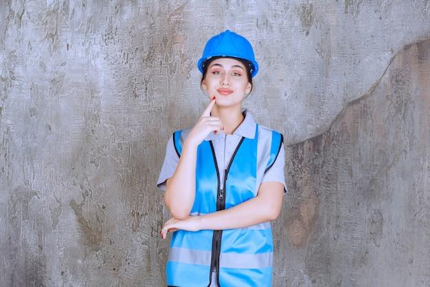 Vrouwelijke ingenieur die een blauwe helm en uitrusting draagt en denkt of plant.