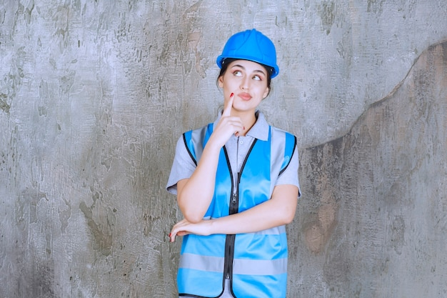 Vrouwelijke ingenieur die een blauwe helm en uitrusting draagt en denkt of plant