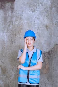 Vrouwelijke ingenieur die een blauwe helm en uitrusting draagt en het hoofd vasthoudt als ze moe is of hoofdpijn heeft.