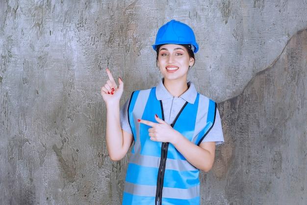 Vrouwelijke ingenieur die een blauwe helm en uitrusting draagt en met emoties naar iets aan de linkerkant wijst.