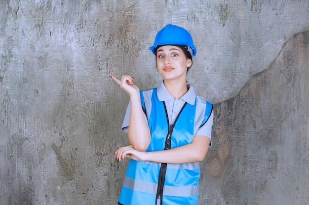 Vrouwelijke ingenieur die een blauwe helm en uitrusting draagt en met emoties naar iets aan de linkerkant wijst