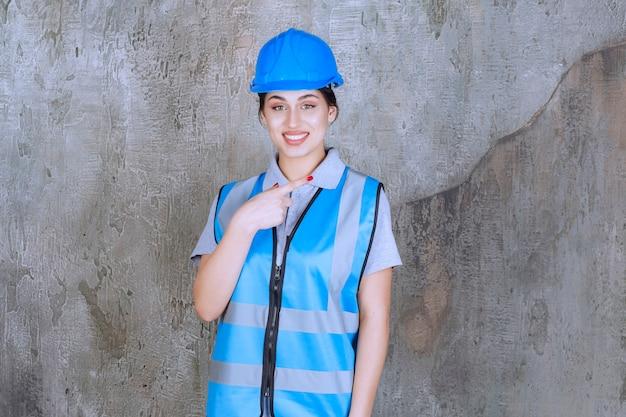 Vrouwelijke ingenieur die een blauwe helm en uitrusting draagt en rechts iets laat zien