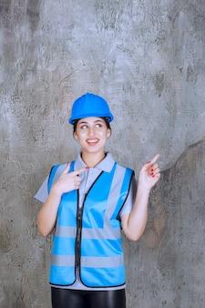 Vrouwelijke ingenieur die een blauwe helm en uitrusting draagt.