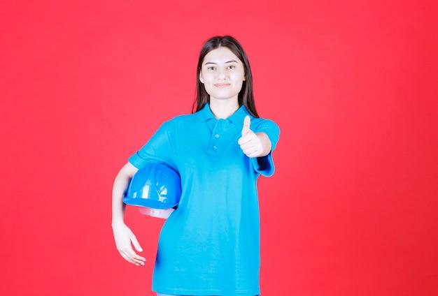 Vrouwelijke ingenieur die een blauwe helm vasthoudt en een positief handteken toont