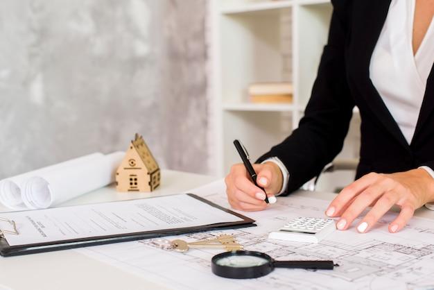 Vrouwelijke ingenieur die een document in haar bureau schrijft
