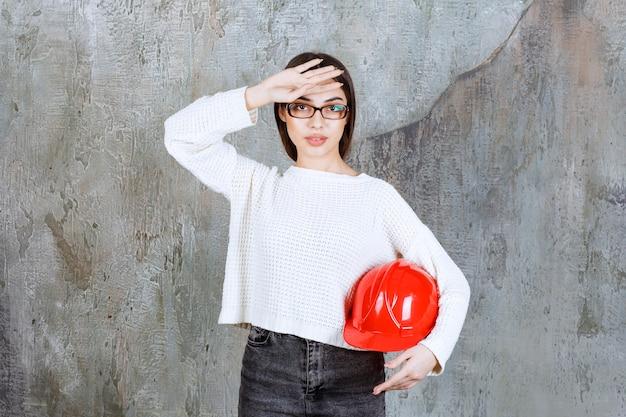 Vrouwelijke ingenieur die een rode helm vasthoudt en er moe uitziet of hoofdpijn heeft.