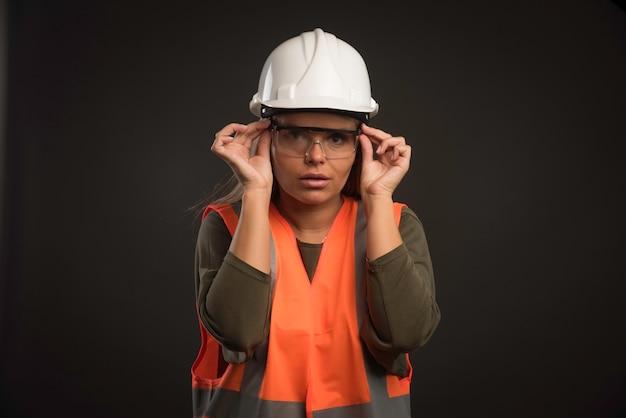 Vrouwelijke ingenieur die een witte helm, een bril en een uitrusting draagt.