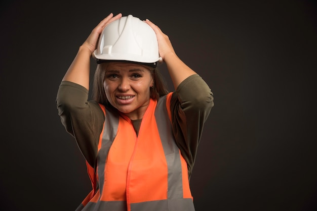 Vrouwelijke ingenieur die een witte helm en een toestel draagt.