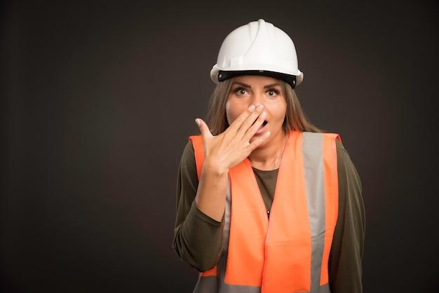 Vrouwelijke ingenieur die een witte helm en uitrusting draagt en kijkt verbaasd.