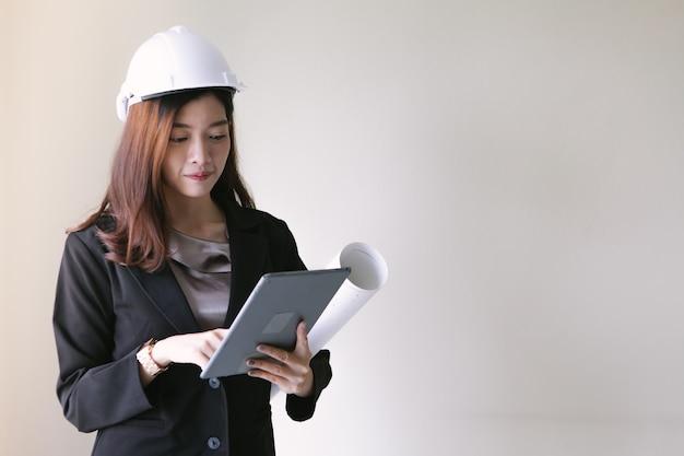 Vrouwelijke ingenieur die een witte helm in haar zwart kostuum draagt.