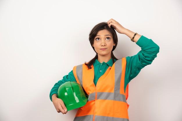 Vrouwelijke ingenieur die haar hoofd krabt en een helm op witte achtergrond houdt.