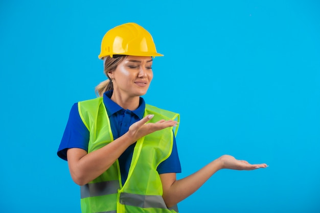 Vrouwelijke ingenieur die in gele helm en toestel iets richt.
