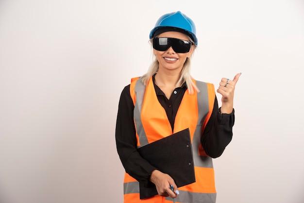 Vrouwelijke ingenieur die in glazen duimen op witte achtergrond maken. hoge kwaliteit foto