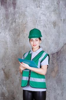Vrouwelijke ingenieur die in groene helm een blauwe omslag houdt.