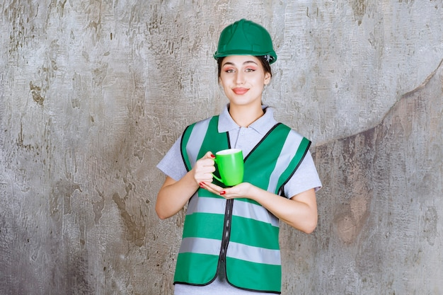 Vrouwelijke ingenieur die in groene helm een groene koffiemok houdt.