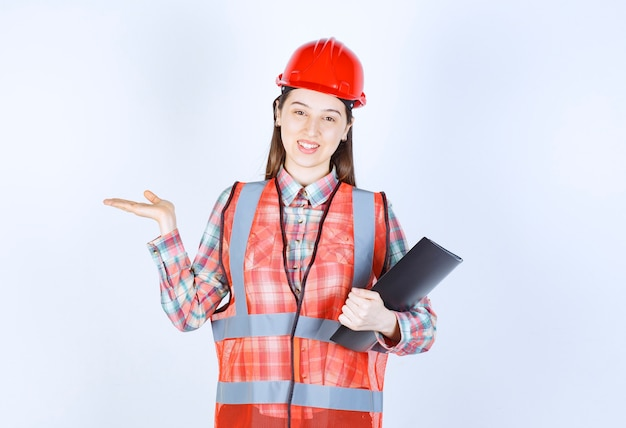 Vrouwelijke ingenieur die in rode helm een zwart projectplan houdt.