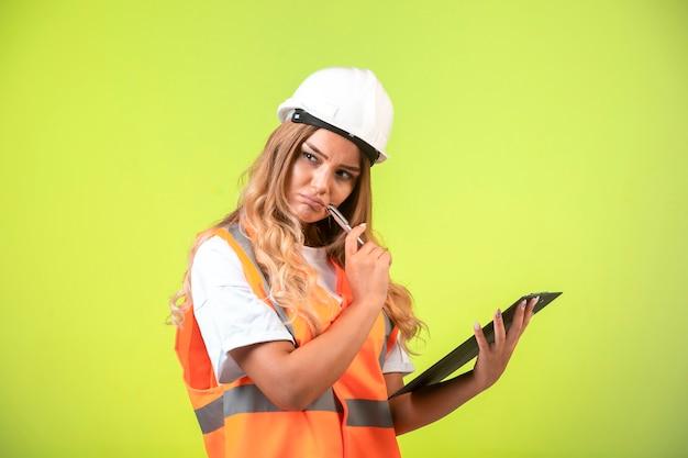 Vrouwelijke ingenieur die in witte helm en toestel de controlelijst houdt en denkt