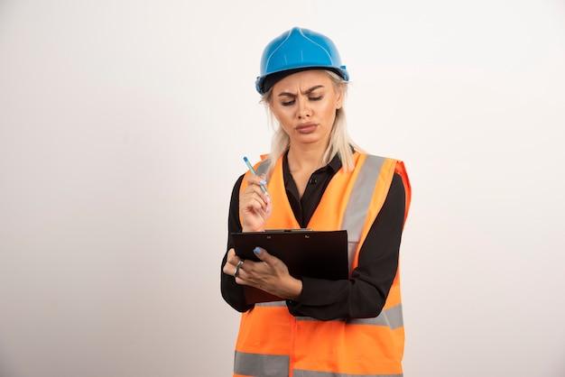 Vrouwelijke ingenieur die nota's op witte achtergrond controleert. hoge kwaliteit foto