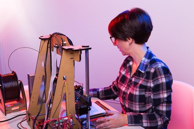 Vrouwelijke ingenieur die 's nachts in het lab werkt, past hij de componenten van een printer aan