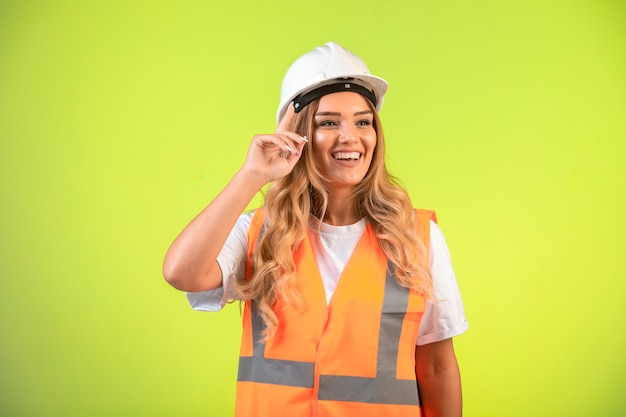 Vrouwelijke ingenieur die verantwoordelijk is in witte helm en uitrusting met een idee