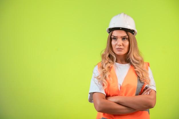 Vrouwelijke ingenieur die verantwoordelijk is in witte helm en uitrusting ziet er agressief uit.