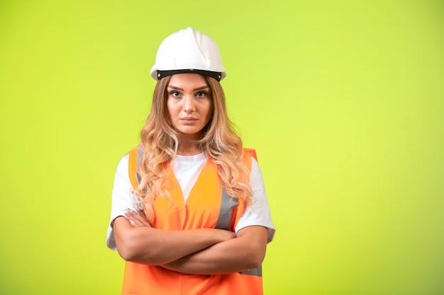 Vrouwelijke ingenieur die verantwoordelijk is in witte helm en uitrusting ziet er professioneel uit.