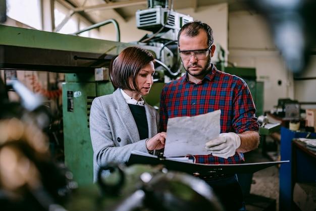 Vrouwelijke ingenieur die zich met machinist bevindt en blauwdruk analyseert