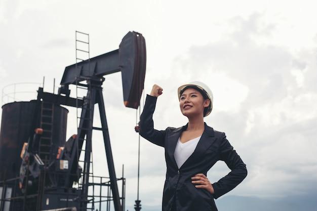 Vrouwelijke ingenieur die zich met werkende oliepompen bevindt met een witte hemel.
