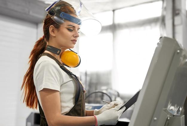 Vrouwelijke ingenieur in beschermende kleding die aan fabriek werkt.