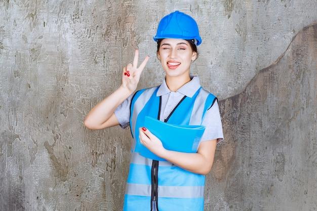 Vrouwelijke ingenieur in blauw uniform en helm die een blauwe rapportmap vasthoudt en een positief handteken toont.