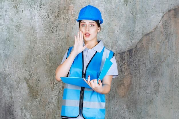 Vrouwelijke ingenieur in blauw uniform en helm die een blauwe rapportmap vasthoudt en iets privé zegt.