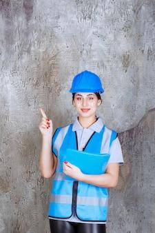 Vrouwelijke ingenieur in blauw uniform en helm die een blauwe rapportmap vasthoudt en naar iemand in de buurt wijst.