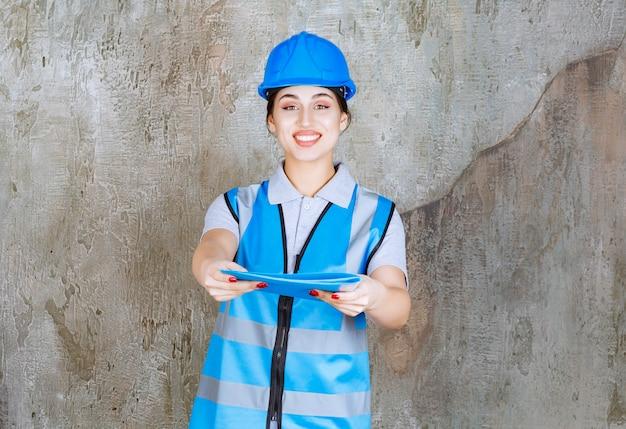 Vrouwelijke ingenieur in blauw uniform en helm die een blauwe rapportmap vasthoudt en ter verificatie geeft